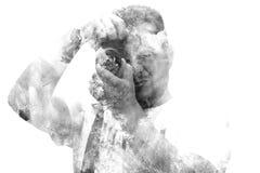 Männlicher Fotograf der Doppelbelichtung, der die Kamera betrachtet Gemaltes Porträt eines Manngesichtes Schwarzweiss-Bild lokali Lizenzfreie Stockfotografie