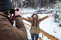 Männlicher Fotograf, der Fotos der glücklichen Frau im Winterwald macht Lizenzfreies Stockfoto