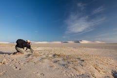 Männlicher Fotograf, der Landschaftsfoto von Sanddünen macht Stockfotografie