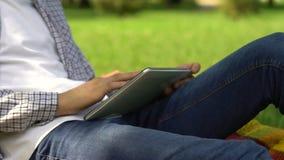 Männlicher Freiberufler, der an Tablette im Sommerpark, Student online sucht Job arbeitet stock video footage