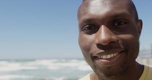 Männlicher Freiwilliger, der Kamera auf dem Strand 4k betrachtet stock video