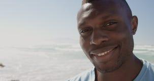 Männlicher Freiwilliger, der Kamera auf dem Strand 4k betrachtet stock video footage