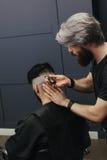 Männlicher Friseur, der Haar eines männlichen Kunden kämmt und rasiert Lizenzfreies Stockfoto