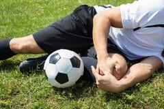 Männlicher Fußball-Spieler, der unter Knie-Verletzung leidet lizenzfreies stockbild