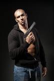 Männlicher Gangster, der ein Gewehr lokalisiert auf Dunkelheit hält Lizenzfreies Stockfoto