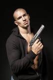 Männlicher Gangster, der ein Gewehr lokalisiert auf Schwarzem hält Lizenzfreie Stockfotografie