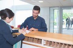 Männlicher Gast, der herauf Formular am Hotelzähler füllt lizenzfreies stockbild