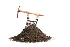 Männlicher Gefangener, der ein Loch gräbt und versucht zu entgehen Lizenzfreies Stockfoto