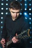 Männlicher Gitarrist, der auf Gitarre auf Stadium spielt Stockbild