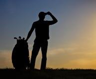 Männlicher Golfspieler bei Sonnenuntergang Stockbild