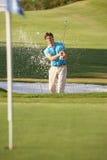 Männlicher Golfspieler, der Bunker-Schuß spielt Stockfotos