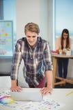 Männlicher Grafikdesigner, der auf Tabelle sich lehnt und Laptop verwendet Stockfotos