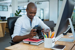 Männlicher Grafikdesigner, der gefangengenommene Bilder in seiner Digitalkamera am Schreibtisch wiederholt stockbild