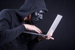 Männlicher Hacker mit tragendem Laptop der schwarzen Maske Stockbild
