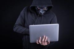 Männlicher Hacker mit tragendem Laptop der schwarzen Maske Stockfoto
