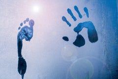 Männlicher Hand- und Fußdruck auf gefrorenem Fensterglas stockfoto