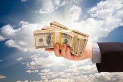 Männlicher Handholding-Stapel Bargeld über Himmel Stockfoto