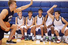 Männlicher Highschool Basketball-Team Having Team Talk With-Trainer Lizenzfreies Stockfoto