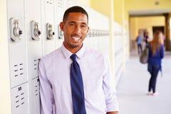 Männlicher Highschoollehrer Standing By Lockers Stockfotografie
