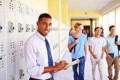 Männlicher Highschoollehrer Standing By Lockers Lizenzfreies Stockfoto