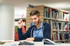 Männlicher Hochschulstudent in der Bibliothek stockfotografie