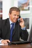 Männlicher Immobilienmakler, der am Telefon am Schreibtisch spricht Stockfotos