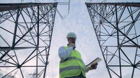 Männlicher Ingenieur betreibt eine Tablette bei der Stellung zwischen Stromleitung Türme stock video footage