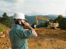 Männlicher Ingenieur, der am Telefon spricht Stockbilder