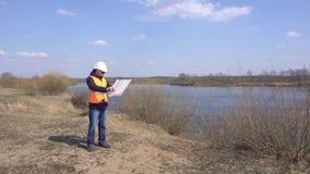 Männlicher Ingenieur in einer Signalweste und in einem Sturzhelm betrachtet einen Plan des seichten Wassers vor dem hintergrund e stock footage