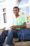 Männlicher Jugendkursteilnehmer, der auf Hochschuljobsteps sitzt Stockfotos