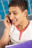Männlicher Jugendkursteilnehmer, der Handy verwendet Stockfotografie