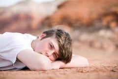 Männlicher Jugendlicher, der auf dem Boden legt Stockfotos
