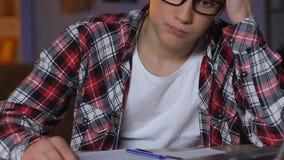 Männlicher Jugendlicher, der die Hausarbeittabelle, mathematisches Problem lösend, hohe Schulbildung tut stock footage