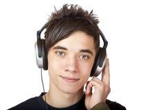 Männlicher Jugendlicher, der zur Musik und zu Lächeln glücklich hört Lizenzfreies Stockbild