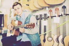 Männlicher Jugendlichkunde, der auf Akustikgitarre entscheidet Stockbild