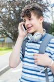 Männlicher Jugendstudent Outside College Building, das auf Mobile spricht Stockfotos