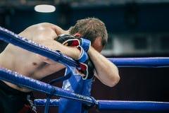 Männlicher Kämpfer von Mischkampfkünsten lehnt sich in der Ecke des Ringes auf seiner Hand Stockfoto