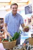 Männlicher Käufer in den Delikatessen organisches Erzeugnis kaufend Lizenzfreies Stockfoto