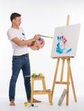 Männlicher Künstler nahe einem Gestell Lizenzfreies Stockfoto
