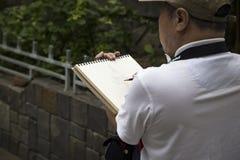 Männlicher Künstler zeichnet eine Skizze der langen Sohn-Pagode Stockbild