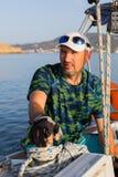 Männlicher Kapitän auf seinem Yachtsegelboot sport Stockfotos