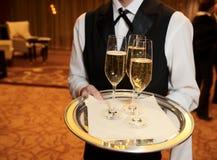 Männlicher Kellner mit Champagnerflöten Stockbilder