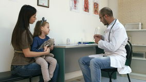 Männlicher Kinderarzt, der Kopftemperatur des kleinen Mädchens mit seiner Hand überprüft und ihren Thermometer gibt stock video