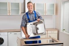 Männlicher Klempner Carrying Sink Lizenzfreie Stockfotografie
