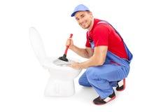 Männlicher Klempner, der eine Toilette mit einem Kolben freimacht Lizenzfreie Stockfotografie