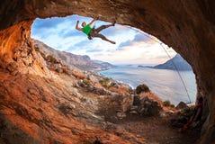 Männlicher Kletterer, der entlang einem Dach in einer Höhle klettert Lizenzfreie Stockbilder