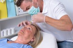 Männlicher Kliniker, der auf Gesicht einer Frau einspritzt Stockfotos