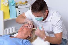 Männlicher Kliniker, der auf Gesicht einer Frau einspritzt Lizenzfreies Stockfoto
