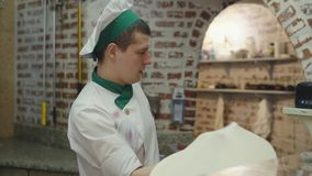 Männlicher Koch dreht Pizzateigkreis stock footage