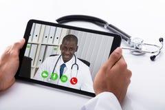 Männlicher Kollege Doktor-Video Conferencing With auf Digital-Tablet stockbilder
